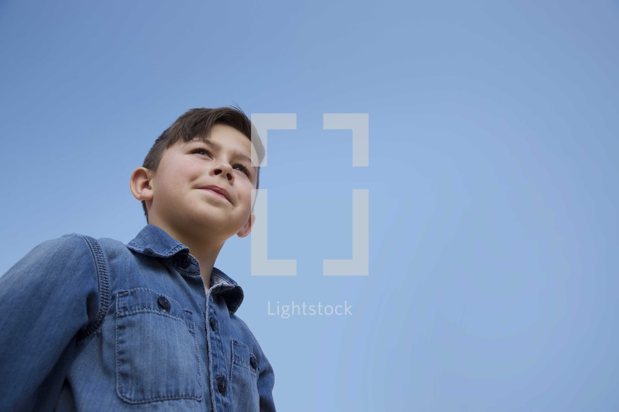 young boy standing under a blue sky