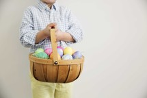 a child holding an Easter basket full of colorful eggs.