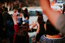 people with hands raised at a worship service
