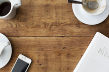 Hero image of Holy Bible, cellphone, coffee cup, and spoon on a table