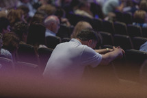 man with head bowed in prayer during a worship service
