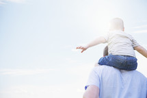 a toddler boy on father's shoulders.