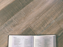 An open Bible on a wood table with negative space.