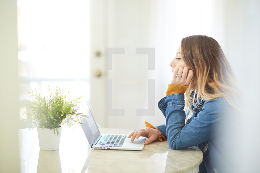 a woman sitting at a kitchen table working at a laptop computer