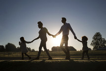 a family walking holding hands down a sidewalk