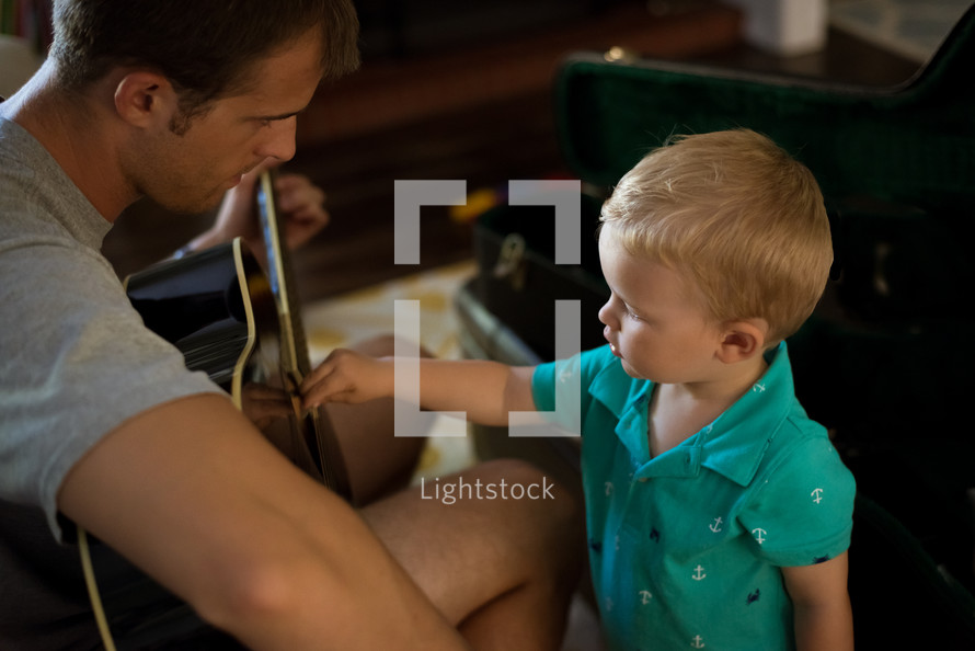 father and toddler son playing a guitar