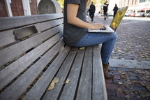 woman sitting on a bench with a laptop on her lap