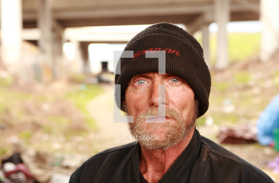 portrait of a homeless man looking directly into the camera