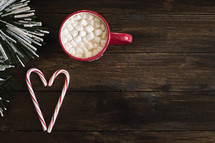 marshmallows and hot cocoa in a red mug and candy canes in the shape of a heart
