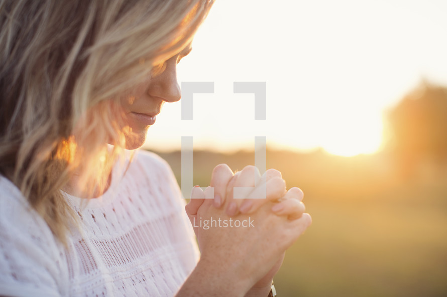 woman with praying hands outdoors at sunrise.