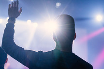 silhouette of a man with hand raised at a concert
