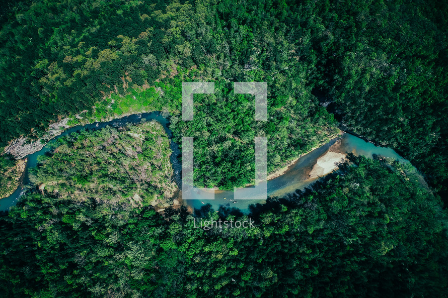 aerial view over a river winding through a forest