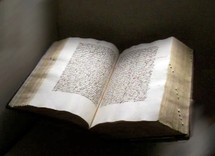 An old bible written in the original Hebrew or Greek manuscript language sitting in a museum with the book open for all to see and read to those who could read the language and understand it.