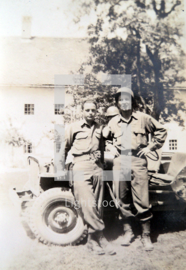 A vintage photograph taken around 1940 - 1944 of two American I soldiers photographed in front of an army jeep while stationed in Normandy, France during World War 2.