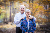 a portrait of an elderly couple in fall outdoors