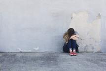 a sad woman crying sitting on a sidewalk