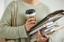 a student holding a coffee cup and books