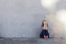 a woman hiding her face sitting on a sidewalk