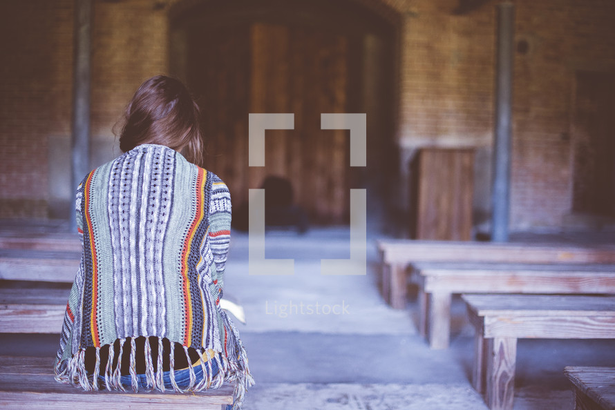 a woman sitting alone in a church