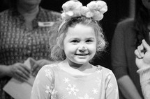 a smiling little girl dressed up as Rudolph