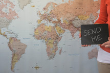 world map and woman holding a send me sign