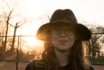 face of a young woman wearing a hat
