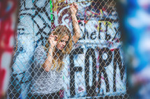 a woman behind a chain link fence and graffiti