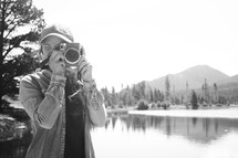 a woman taking a picture with a camera standing in front of a lake