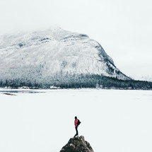snow on a mountain and woman standing on a rock peak