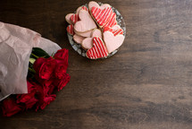 bouquet of red roses and heart shaped cookies