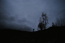 A silhouette of a man backpacking.