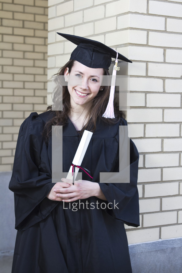College student at graduation with a diploma, cap, and gown