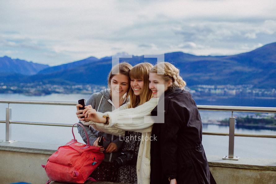 friends taking a selfie with mountains in the background