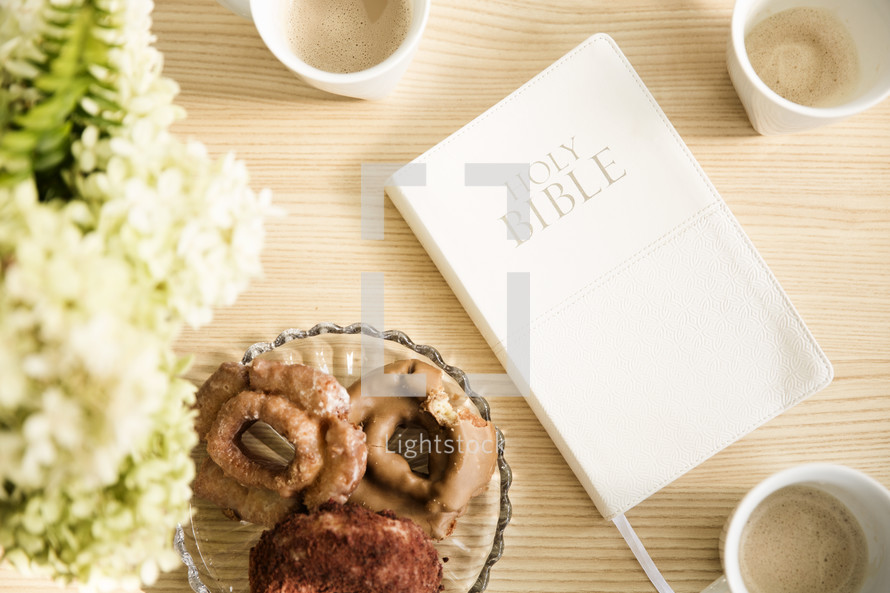 Bible and a plate of donuts on a table.