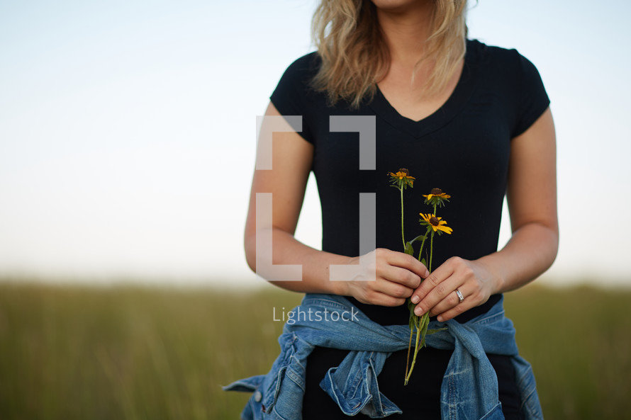 a young woman standing in a field of tall grass holding flowers