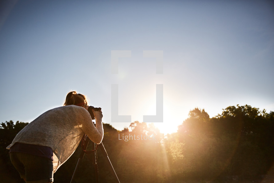 a woman taking a picture of the sunset with her camera