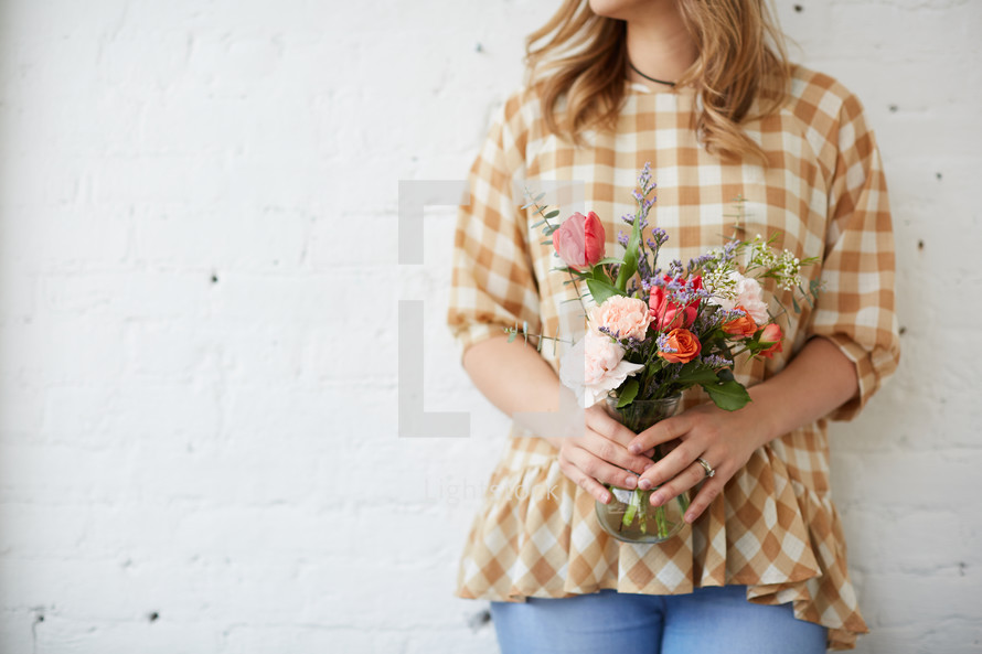a woman holding a vase of flowers