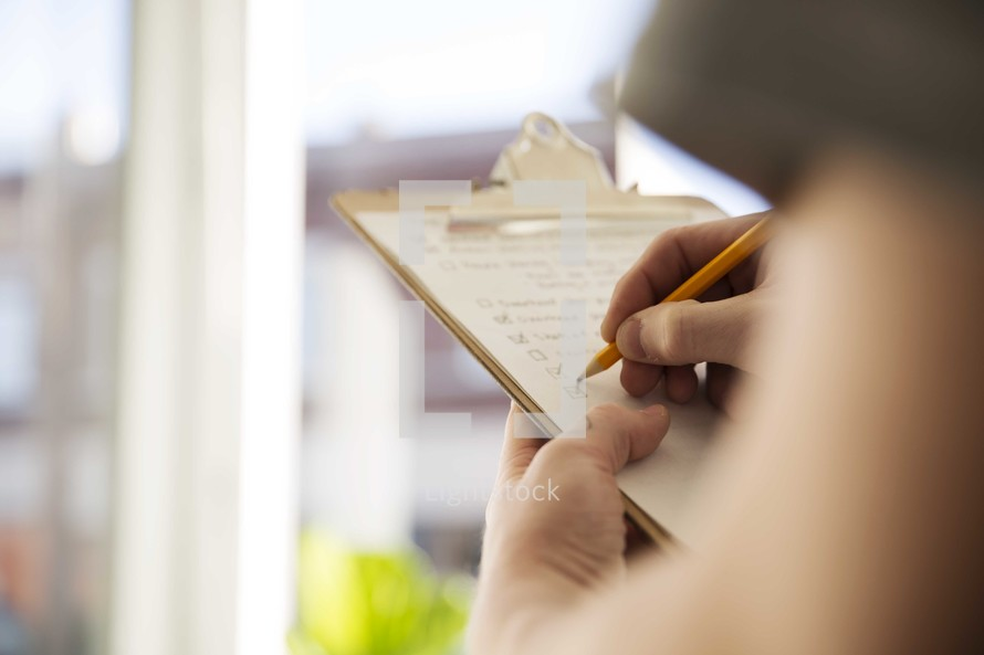man checking off items on a check list