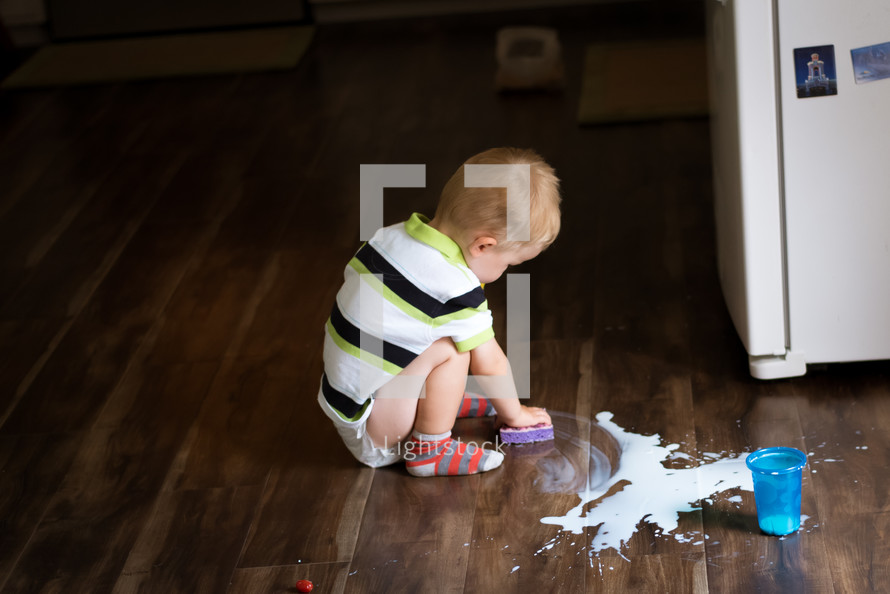 toddler boy cleaning up spilt milk