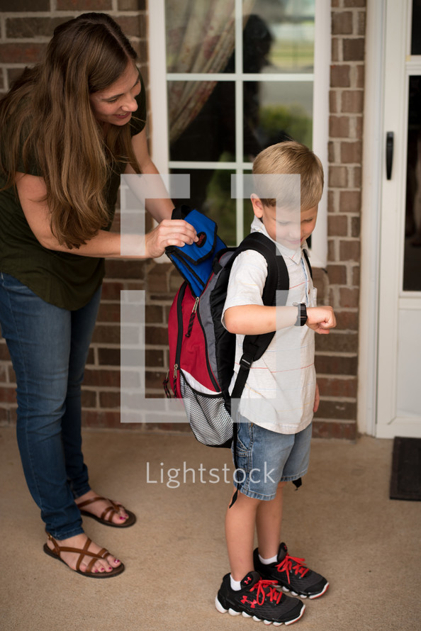 mother helping a child get ready for school