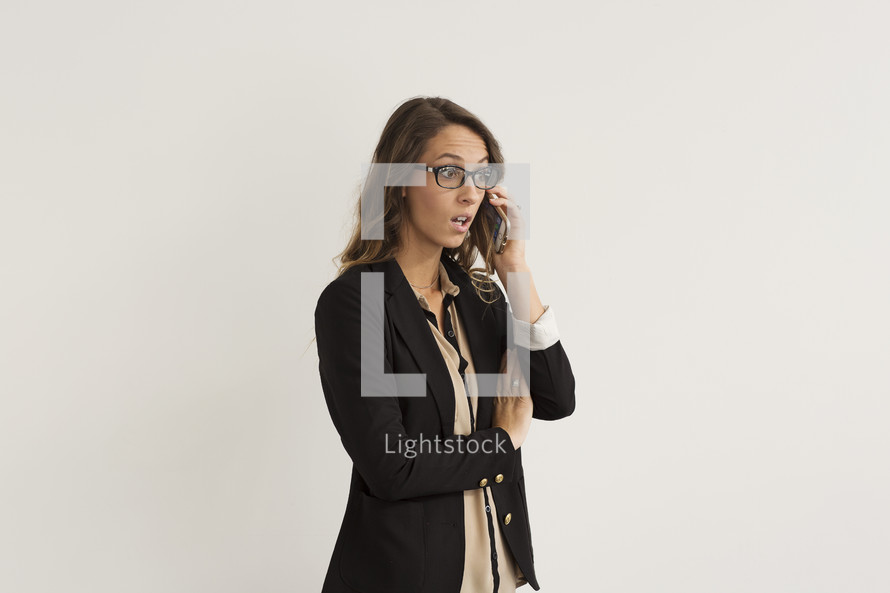 a shocked young woman talking on a cellphone
