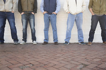 Men's group standing against a wall.