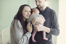 Husband and wife hold infant.
