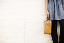 torso of a girl holding a suitcase