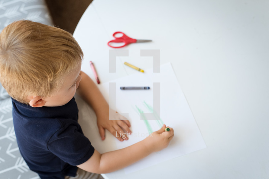 a boy coloring with crayons