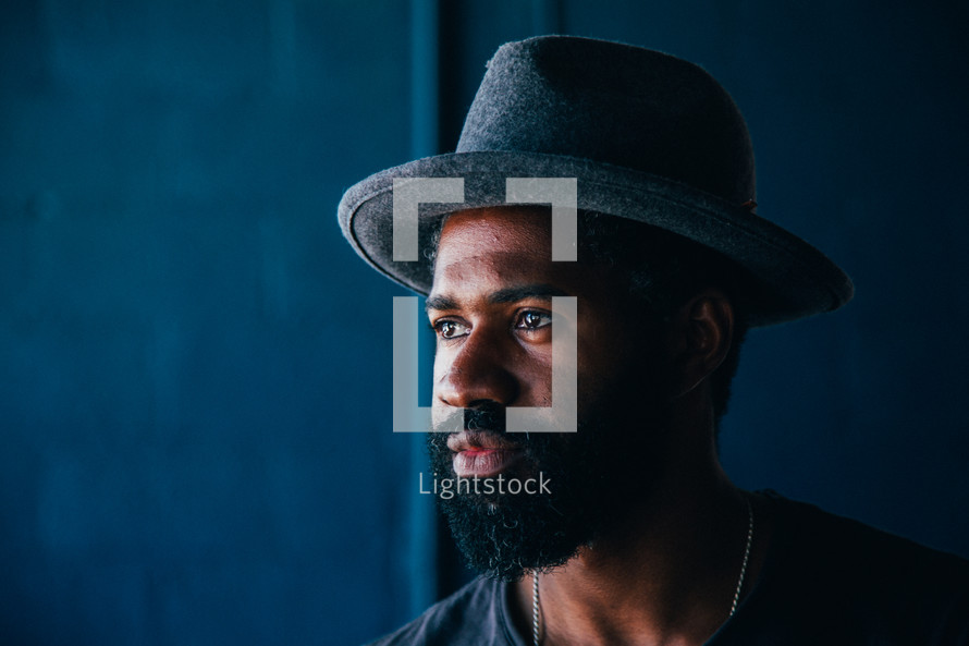 African American man with a thick beard wearing a hat