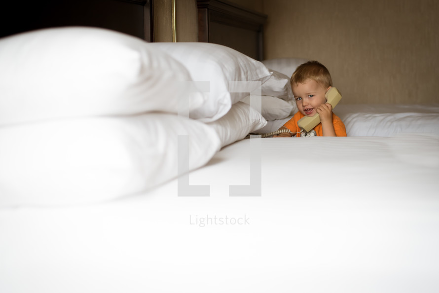a little boy talking on a telephone in a hotel room
