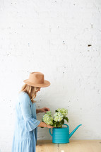 a woman arranging hydrangeas in a watering can on a table