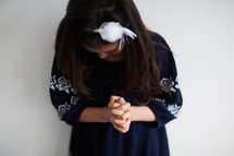 a little girl with head bowed in prayer
