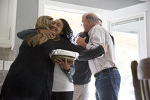 Parents greeting young couple as they come home.